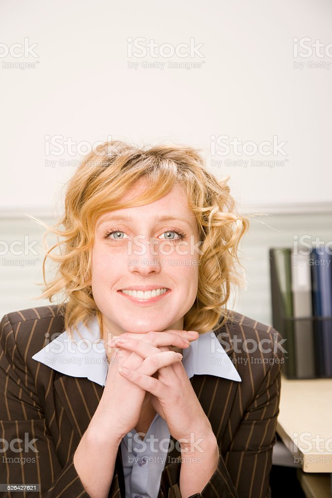 Woman sitting at desk in office, smiling, portrait stock photo