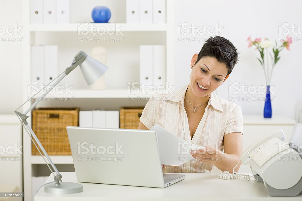 Woman sitting at desk reading business document royalty-free stock photo