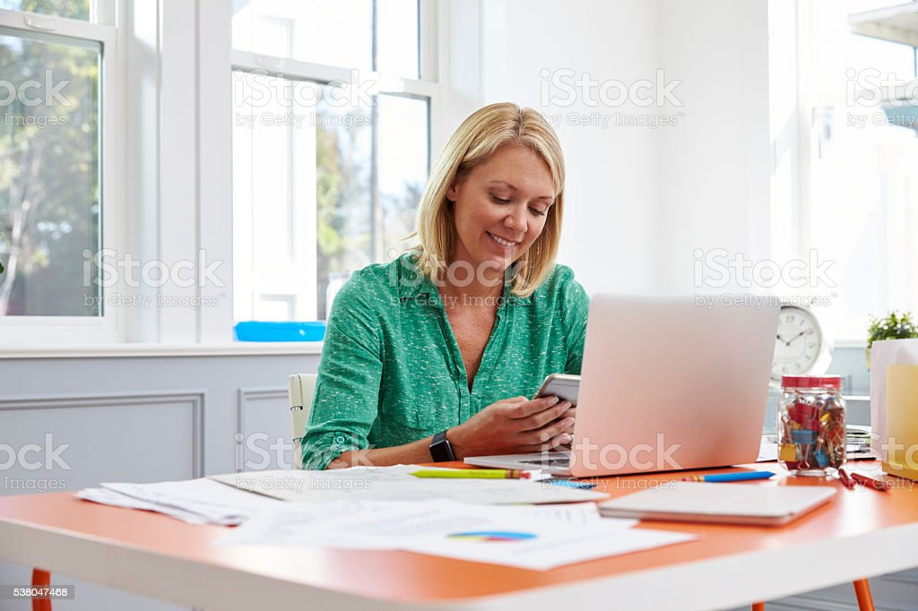 Woman Sitting At Desk Using Mobile Phone In Home Office stock photo