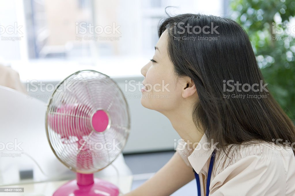 Woman sitting at desk with an electric fan stock photo
