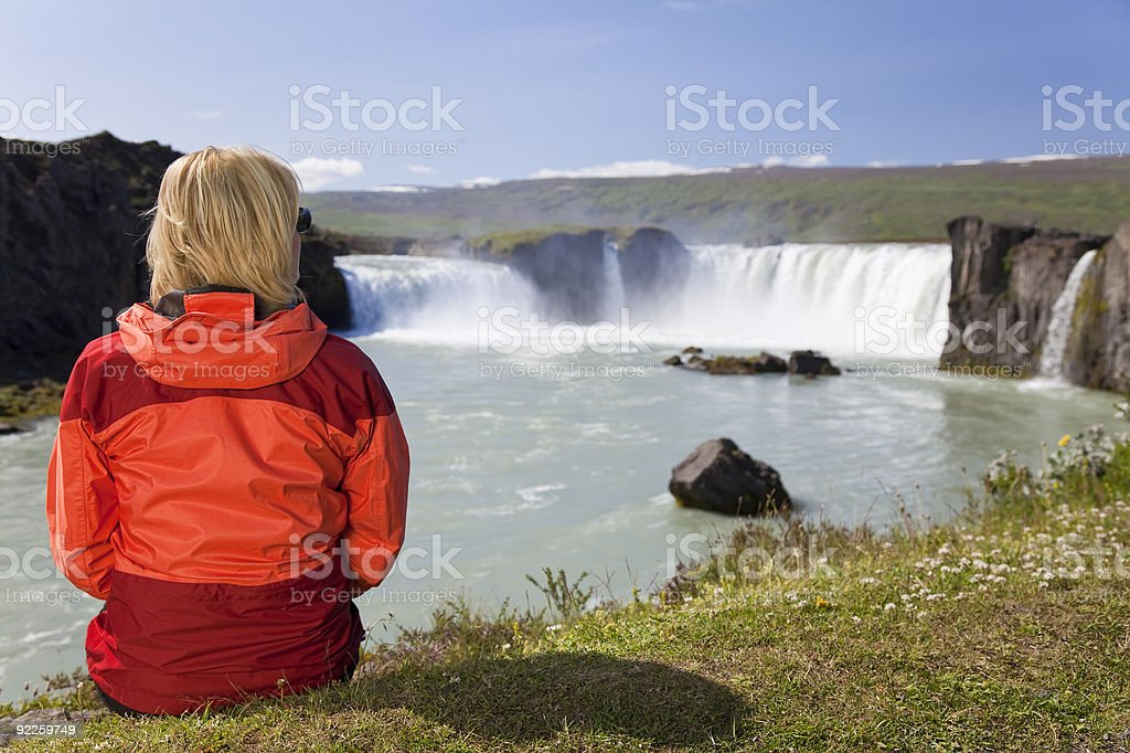 Woman Sitting At Godafoss Waterfall In Iceland royalty-free stock photo