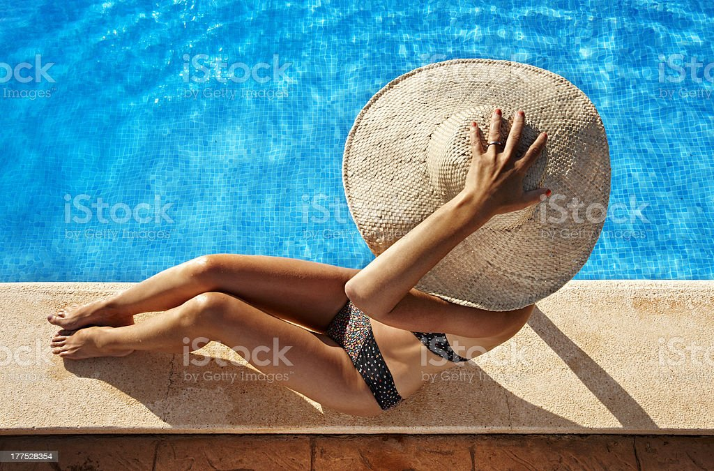 Woman sitting at poolside royalty-free stock photo