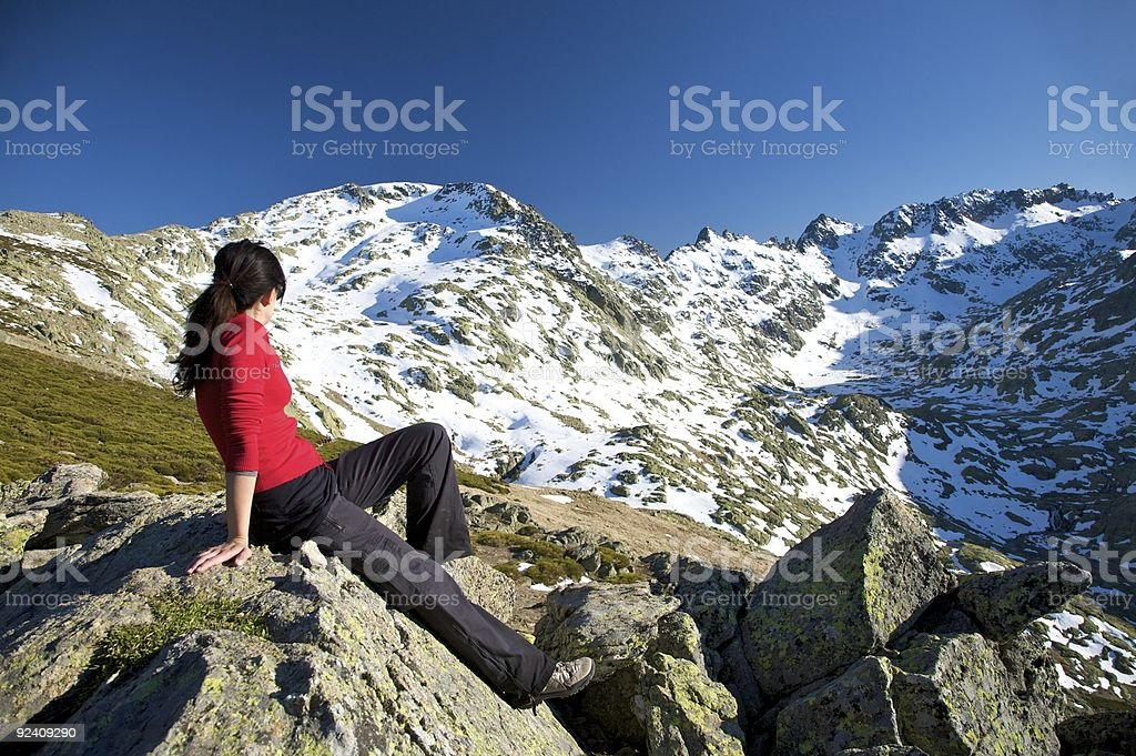 woman sitting at rock top watching snow summit mountains royalty-free stock photo
