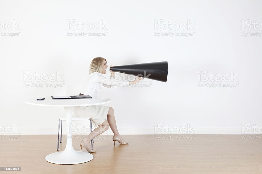 Woman sitting at table shouting into huge megaphone royalty-free stock photo