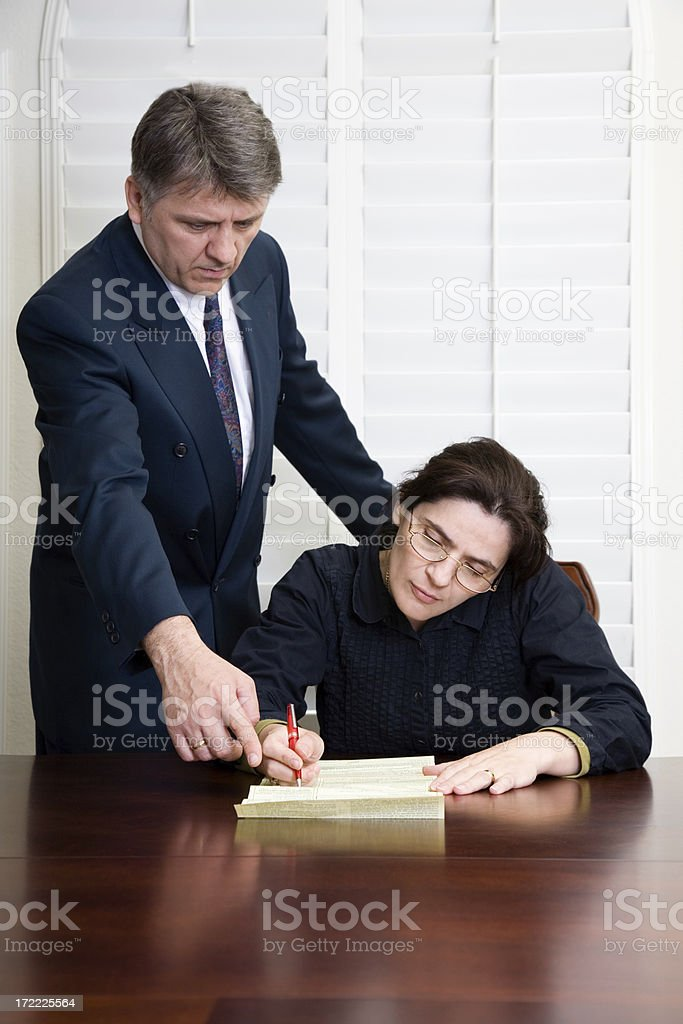Woman sitting at table writing with a man looking over her. royalty-free stock photo