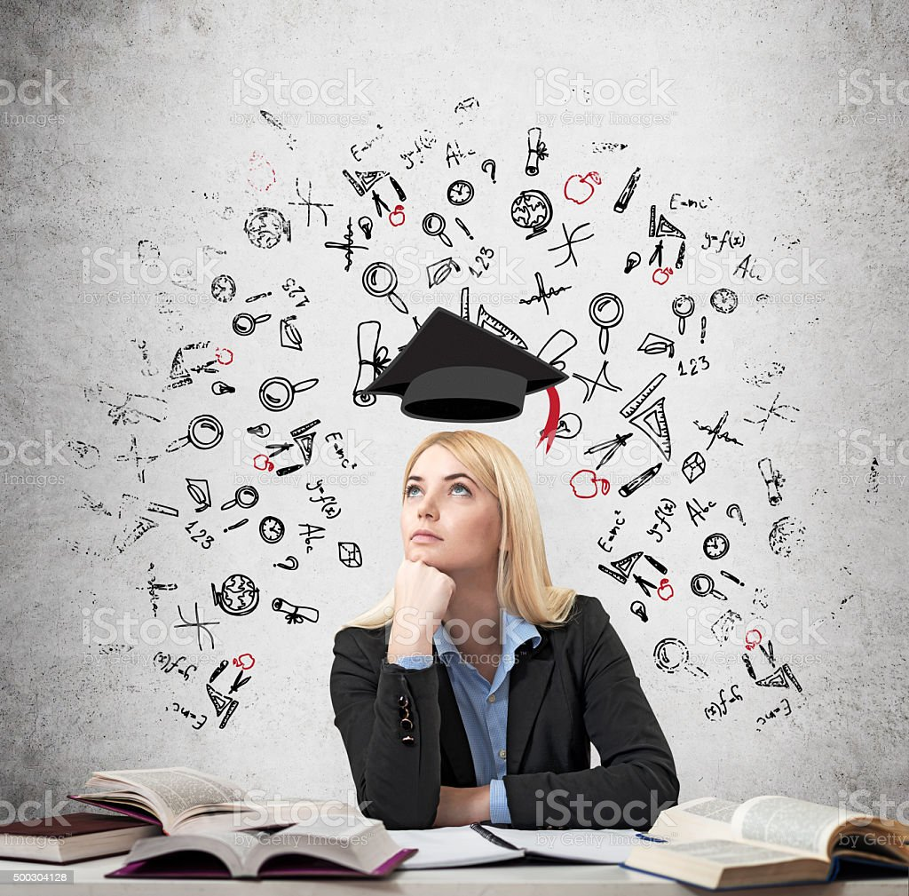 woman sitting at the desk with books around thinking education stock photo