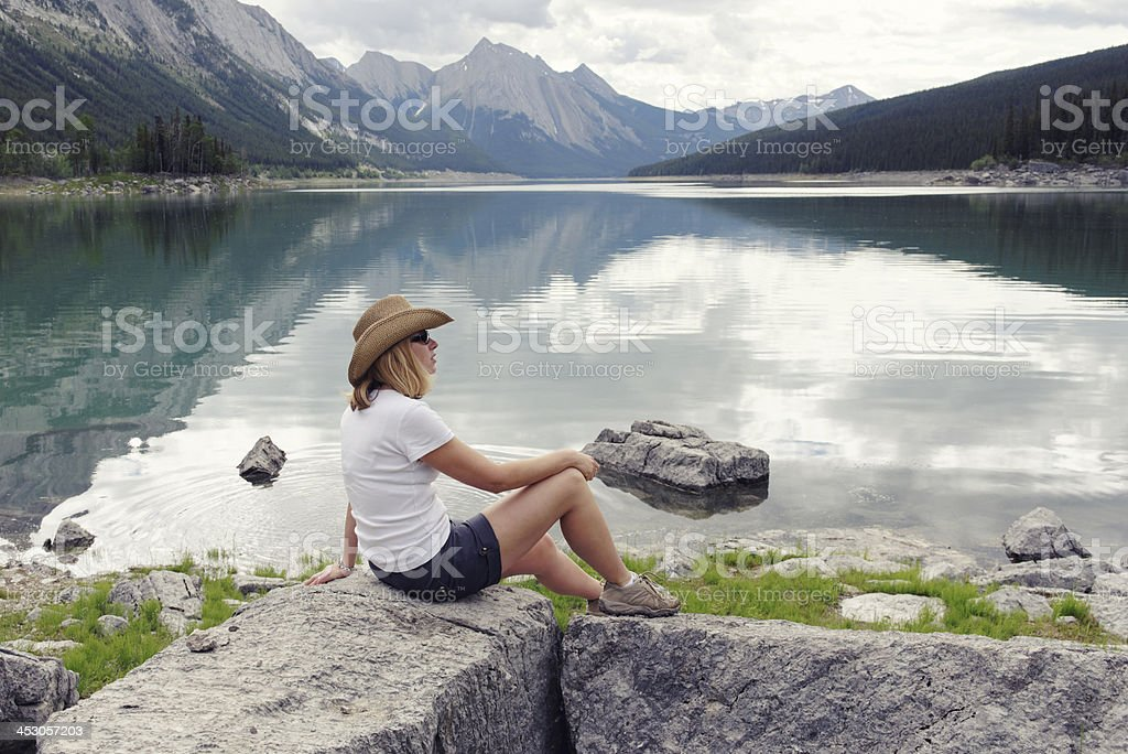 Woman sitting at the edge of Medicine Lake royalty-free stock photo