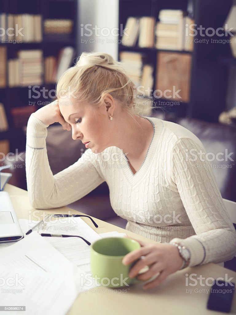 woman sitting at the table and working at home stock photo