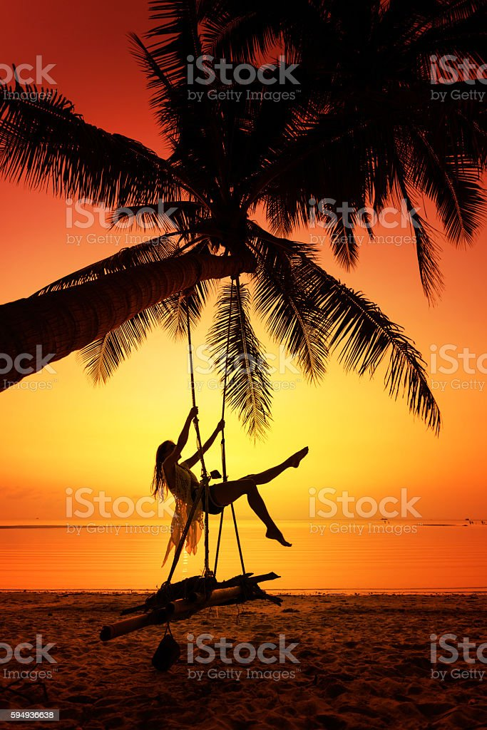 Woman sitting at tropical swing stock photo
