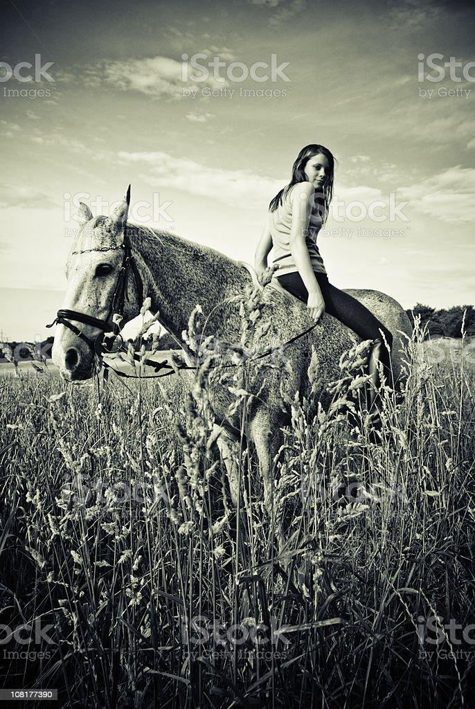 Woman Sitting Backwards on Horse stock photo