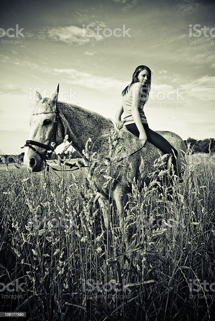 Woman Sitting Backwards on Horse stock photo