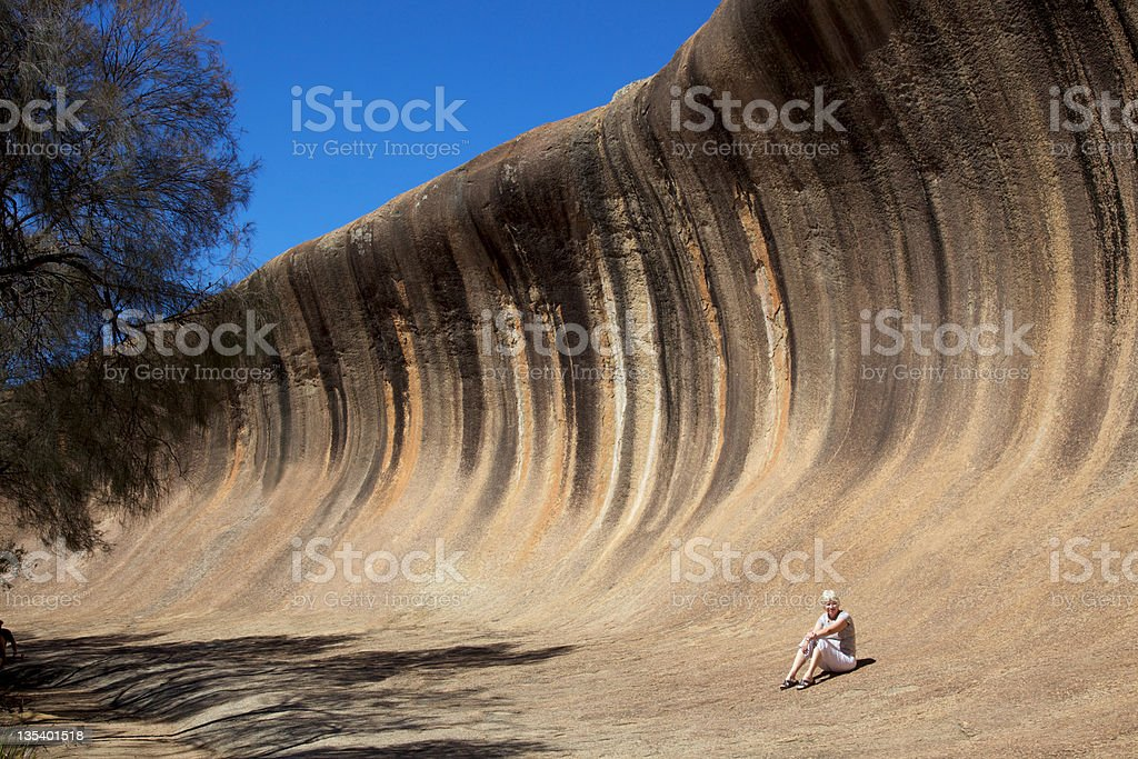 Woman sitting beneath awesome Wave Rock formation stock photo