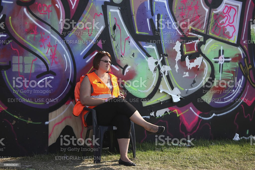 Woman sitting by a huge graffiti on Roskilde Festival stock photo