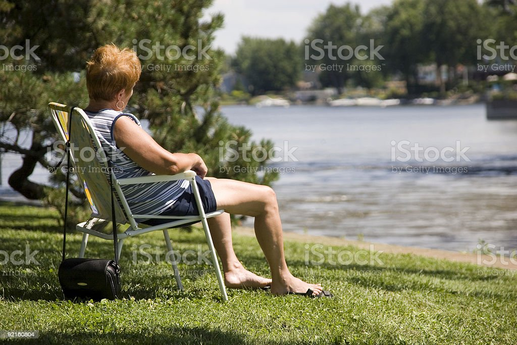 Woman sitting by a river royalty-free stock photo