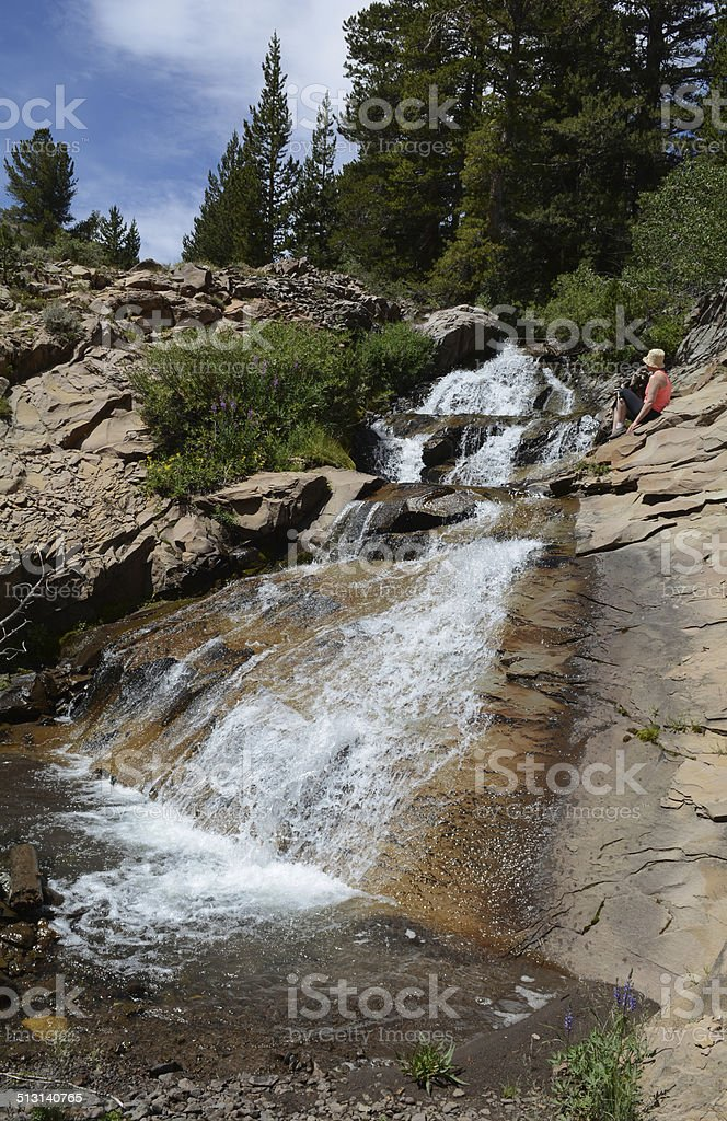 Woman Sitting by a Waterfall royalty-free stock photo