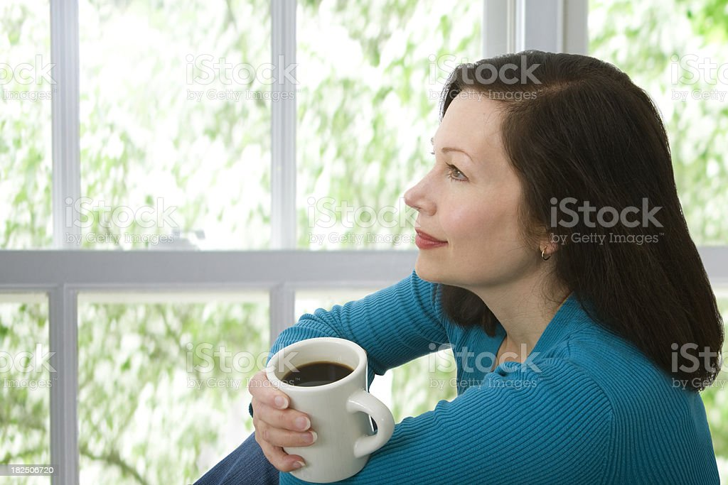 woman sitting by a window with coffee royalty-free stock photo