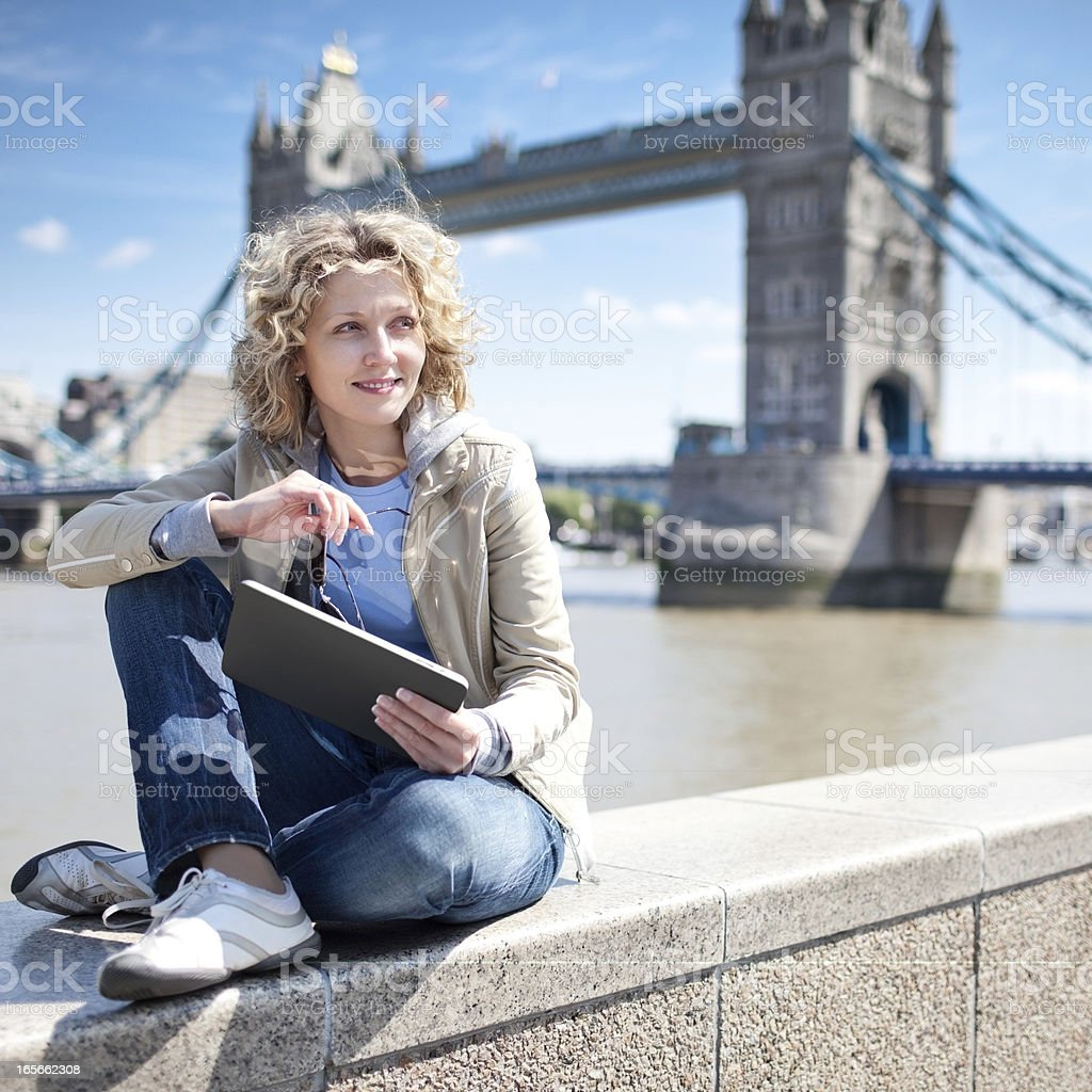 Woman sitting by the river using a tablet royalty-free stock photo