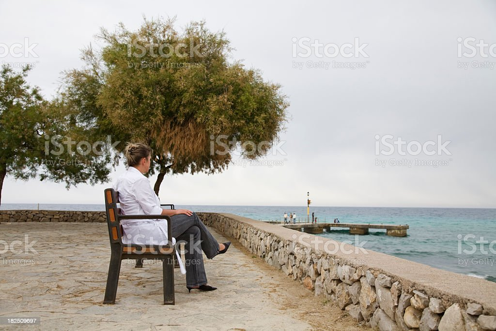 Woman sitting by the seaside royalty-free stock photo