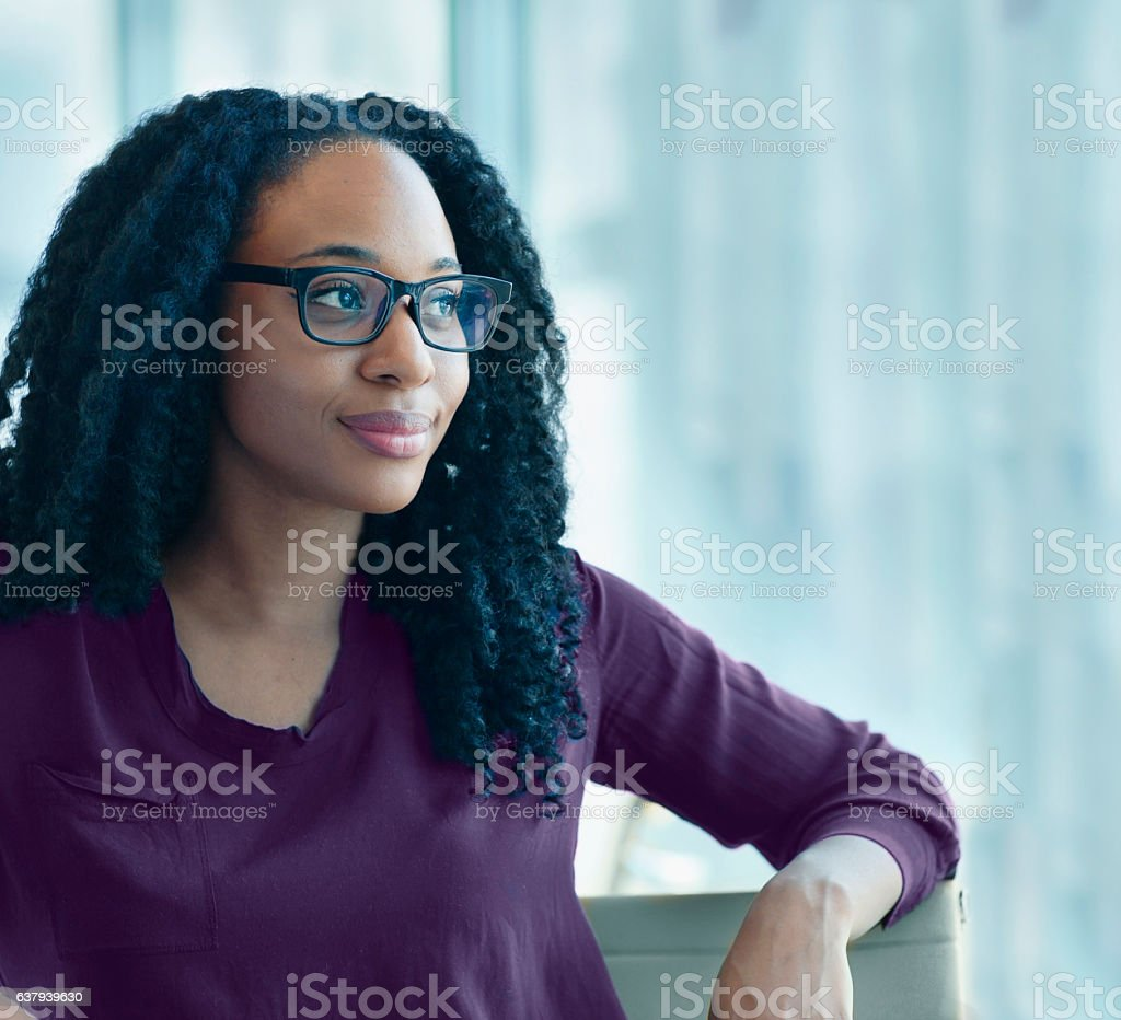 Woman sitting confidently in office looking out of window stock photo