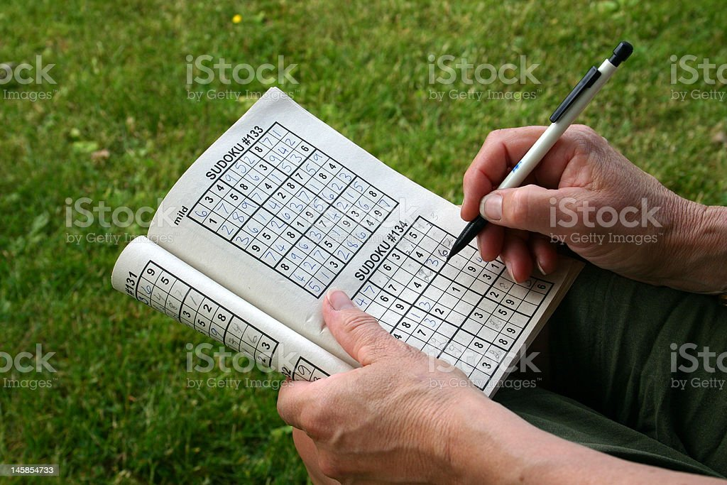 Woman sitting doing a Sudoku Puzzle stock photo