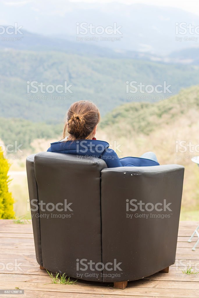 Woman sitting in a armchair stock photo