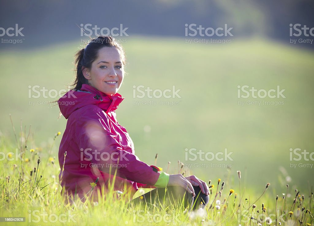 Woman sitting in a meadow on a spring day royalty-free stock photo