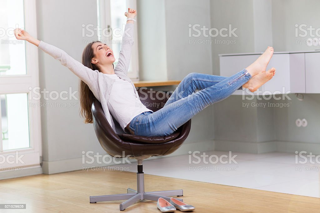 Woman sitting in armchair, arms outstretched stock photo
