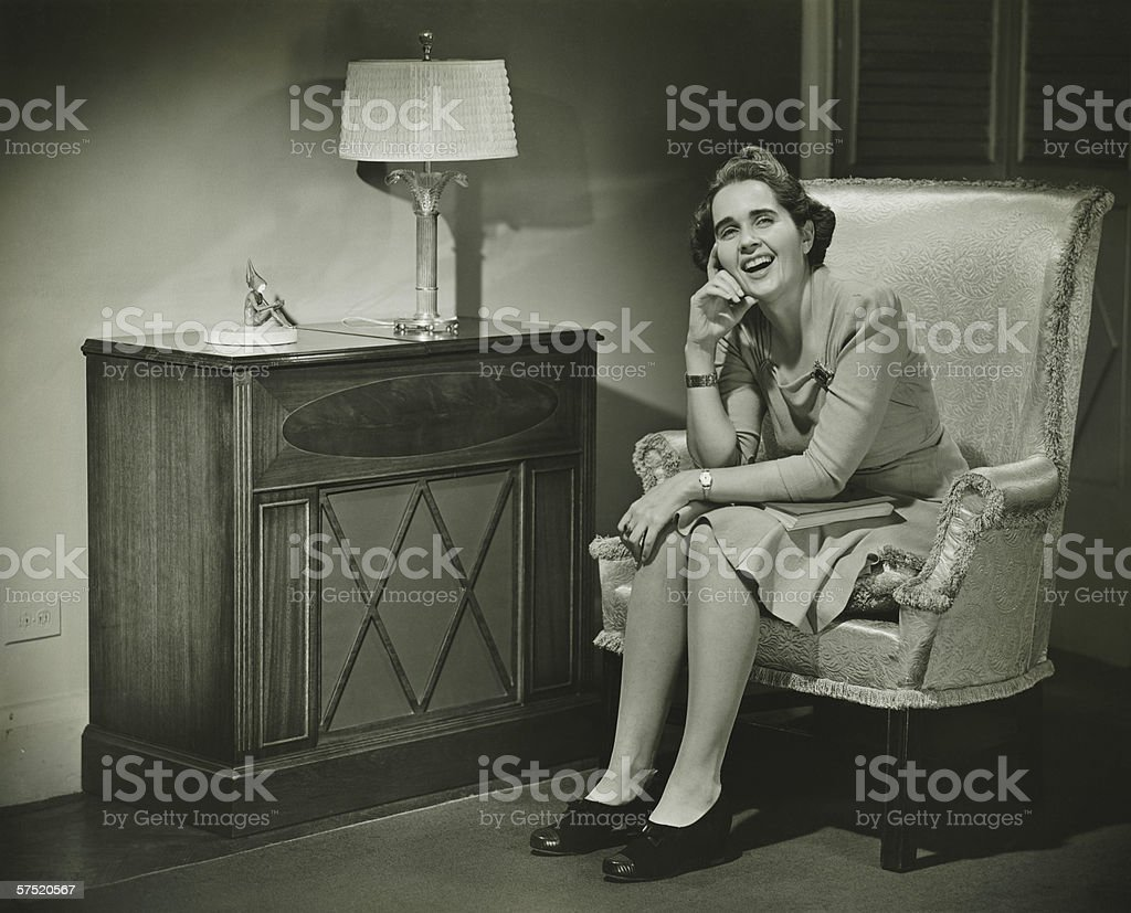 Woman sitting in armchair, smiling, (B&W) stock photo