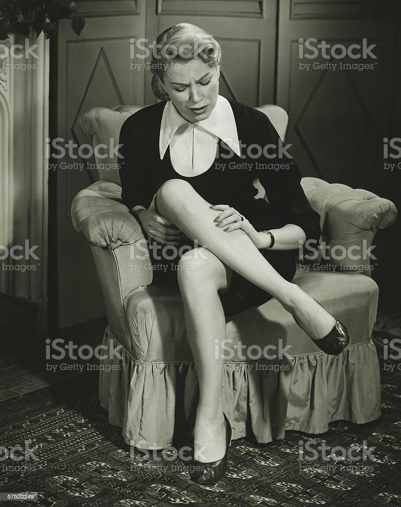 Woman sitting in armchair, watching leg, (B&W) stock photo
