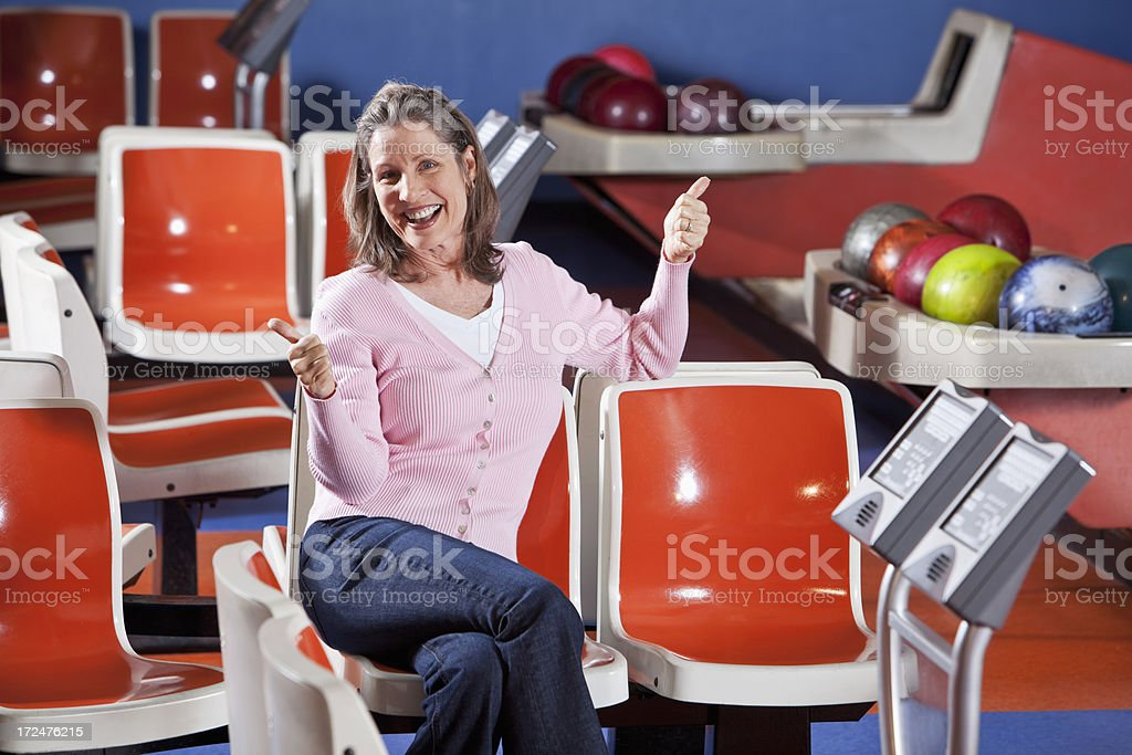 Woman sitting in bowling alley stock photo