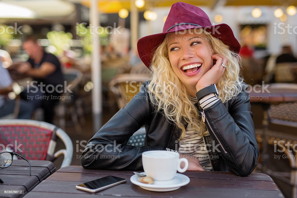 Woman sitting in cafe and laughing stock photo