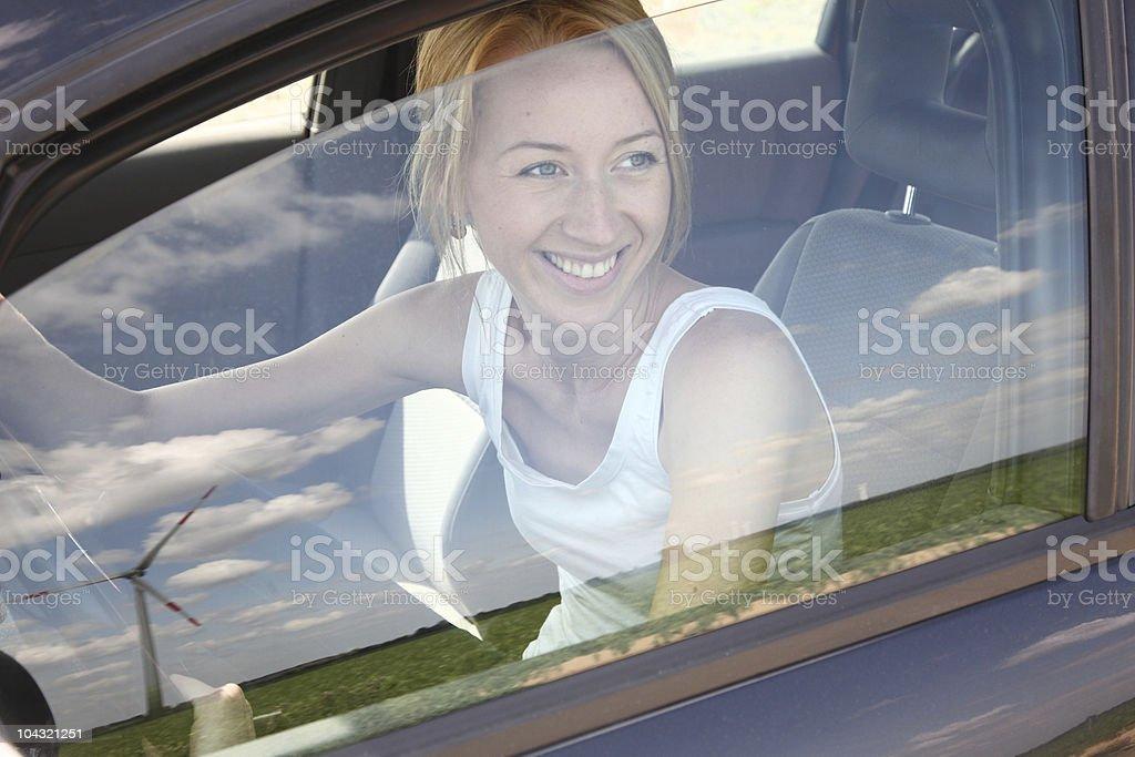 woman sitting in car an look to wind turbine stock photo