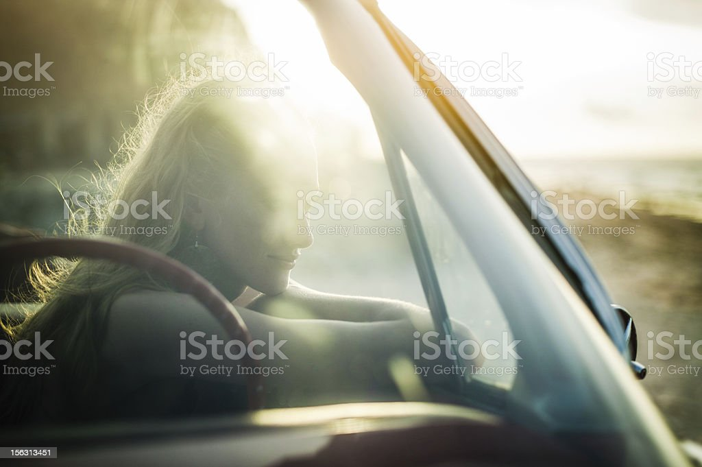 Woman sitting in car watching sunset stock photo