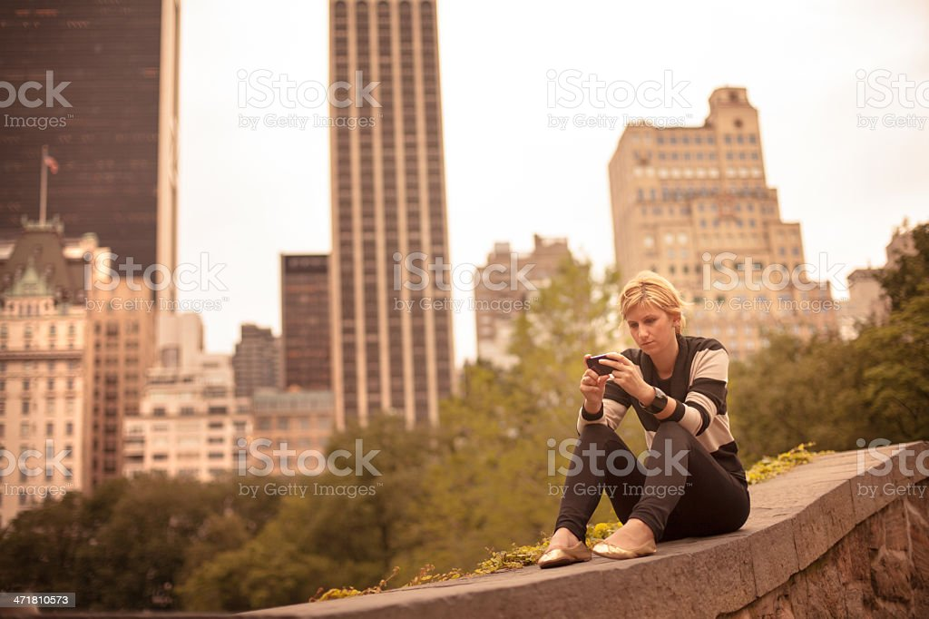 Woman sitting in Central Park with smart phone royalty-free stock photo