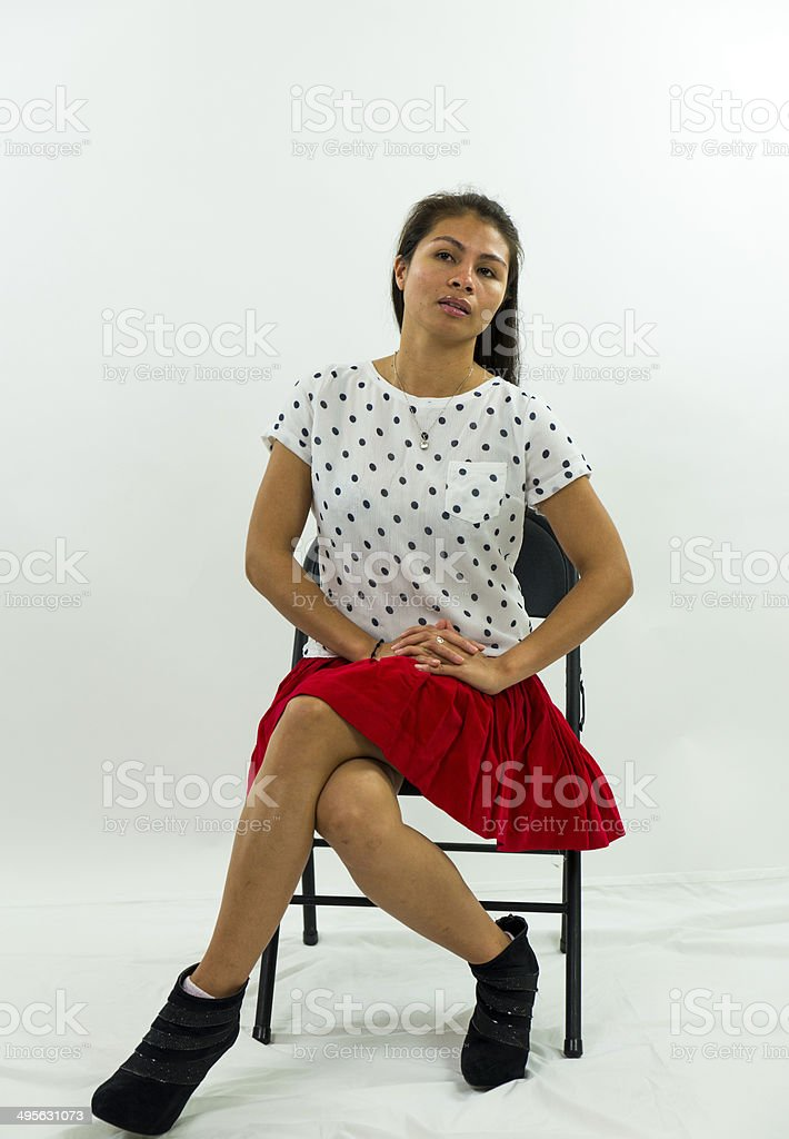 Woman Sitting In Chair Hands In Her Lap Serious Look stock