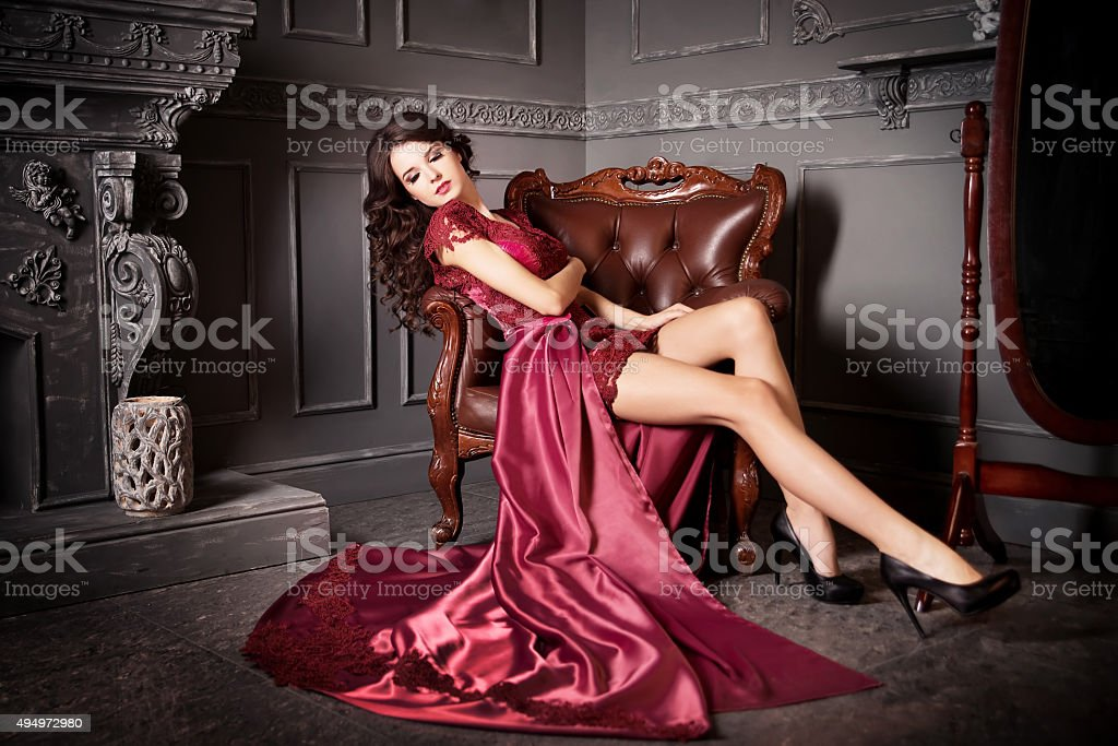 Woman sitting in chair in long claret, purple dress. Luxury stock photo