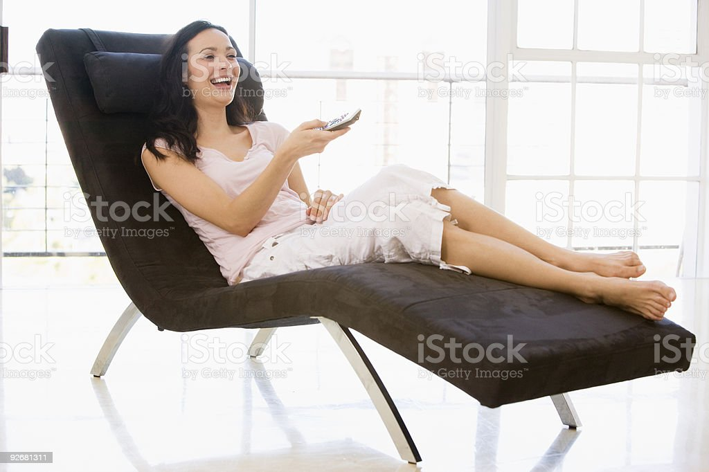 Woman sitting in chair using remote royalty-free stock photo