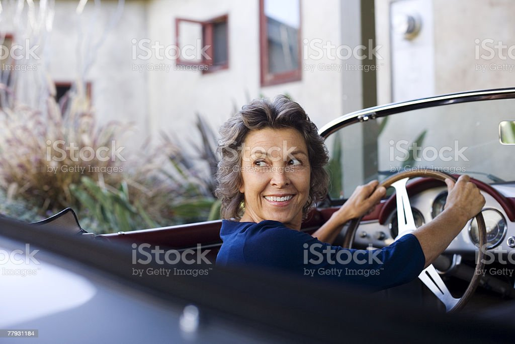 Woman sitting in convertible car smiling over her shoulder royalty-free stock photo