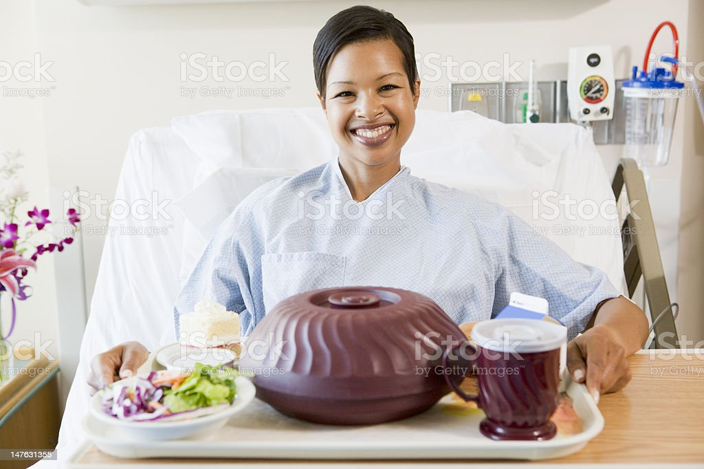 Woman Sitting In Hospital Bed With A Tray Of Food stock photo
