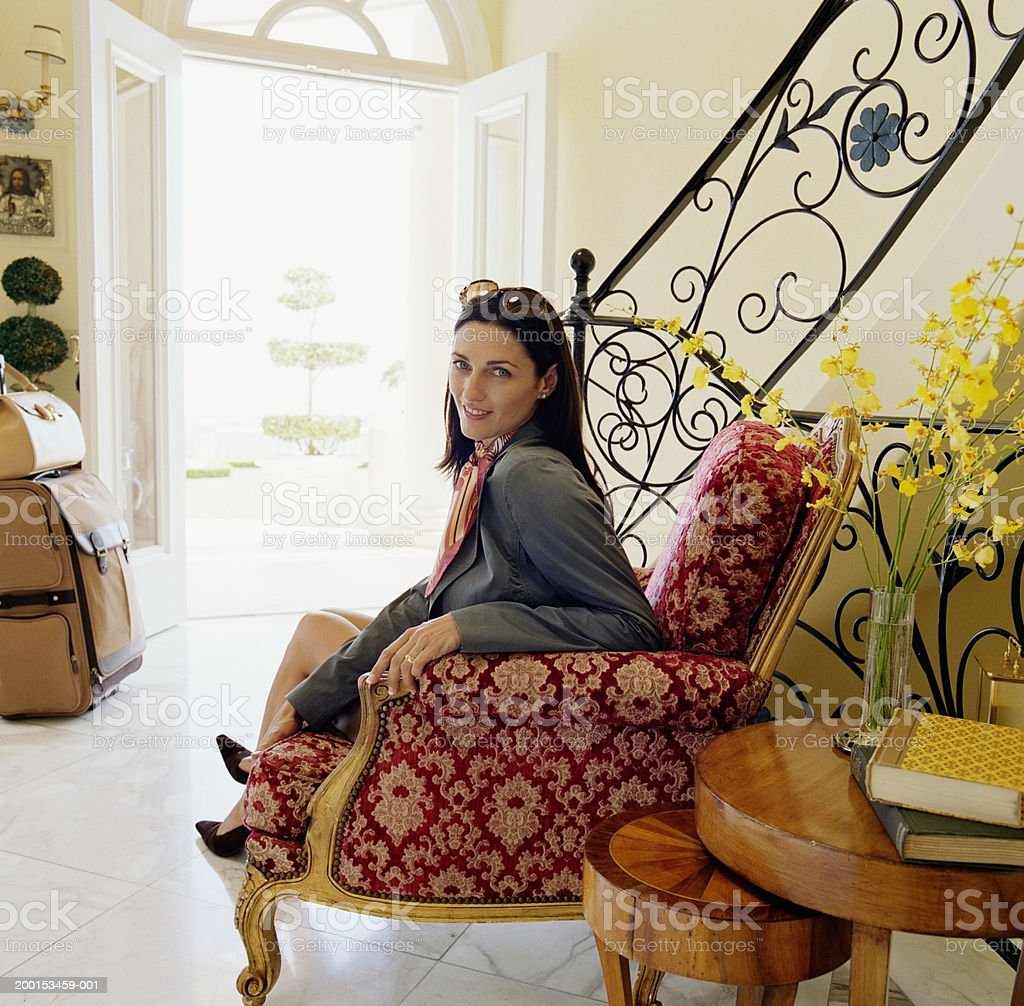 Woman sitting in hotel lobby, portrait stock photo