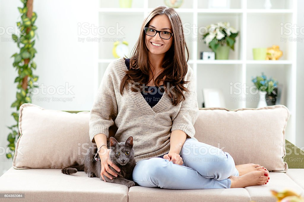 Woman sitting in living room with cat stock photo