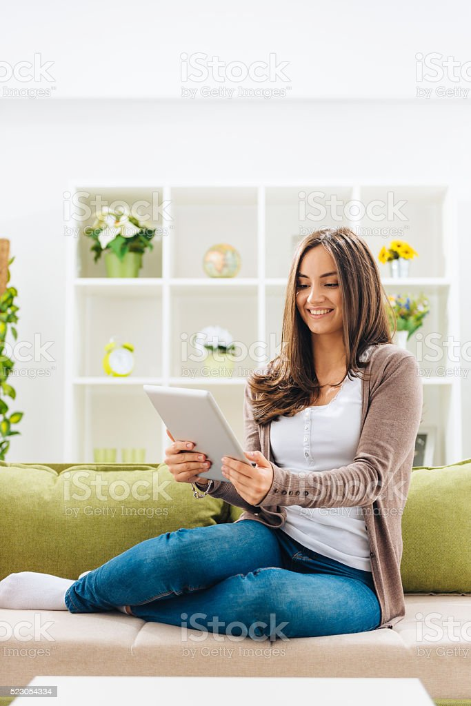 Woman sitting in living room with digital tablet and smiling stock photo