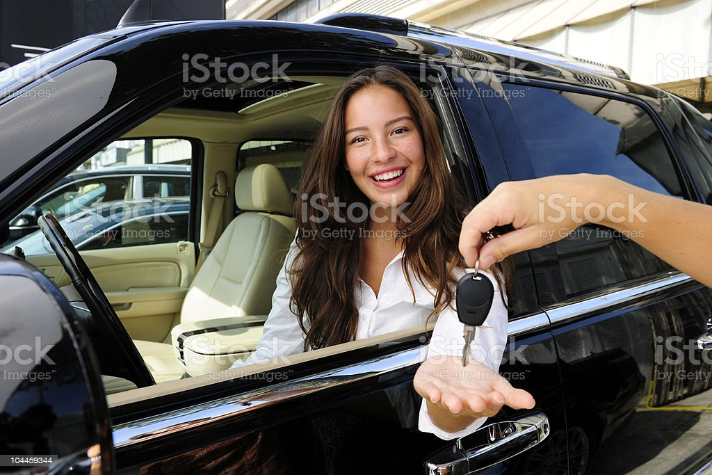 Woman sitting in new status car and receiving keys stock photo