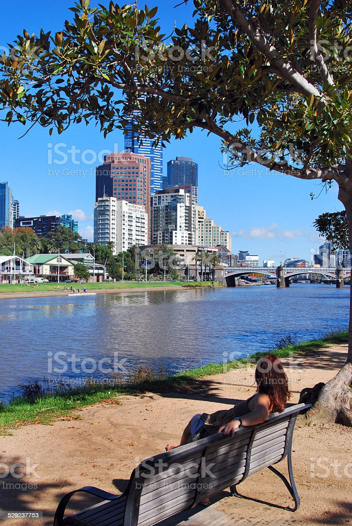 Woman sitting in park by Yarra River, Melbourne, Australia stock photo