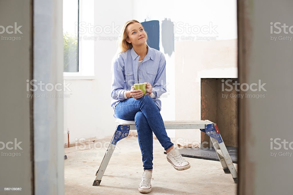 Woman Sitting In Property Being Renovated stock photo