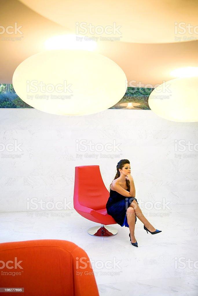 Woman Sitting in Red Chair stock photo