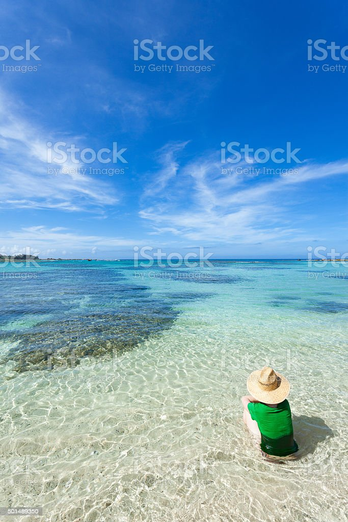 Woman sitting in shallow clear water of tropical beach, Japan stock photo