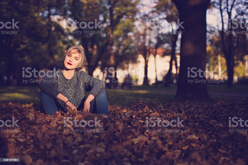 Woman sitting in the leaves stock photo
