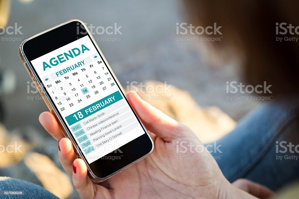woman sitting in the street holding her smartphone achecking age stock photo