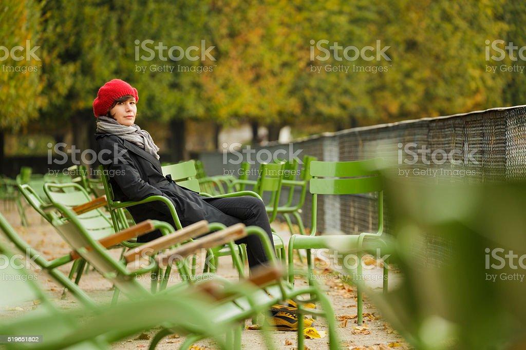 Woman sitting in Tuileries Garden in Paris, France. stock photo